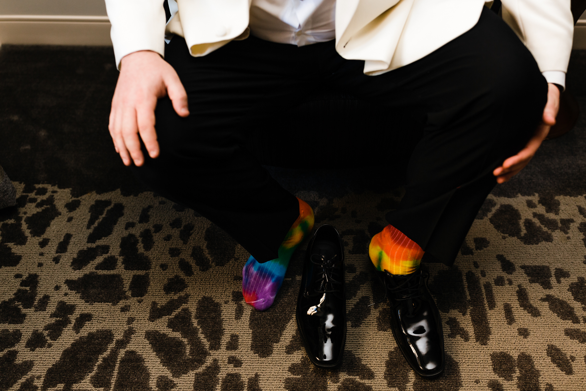 Groom puts on his shoes with tie dye socks