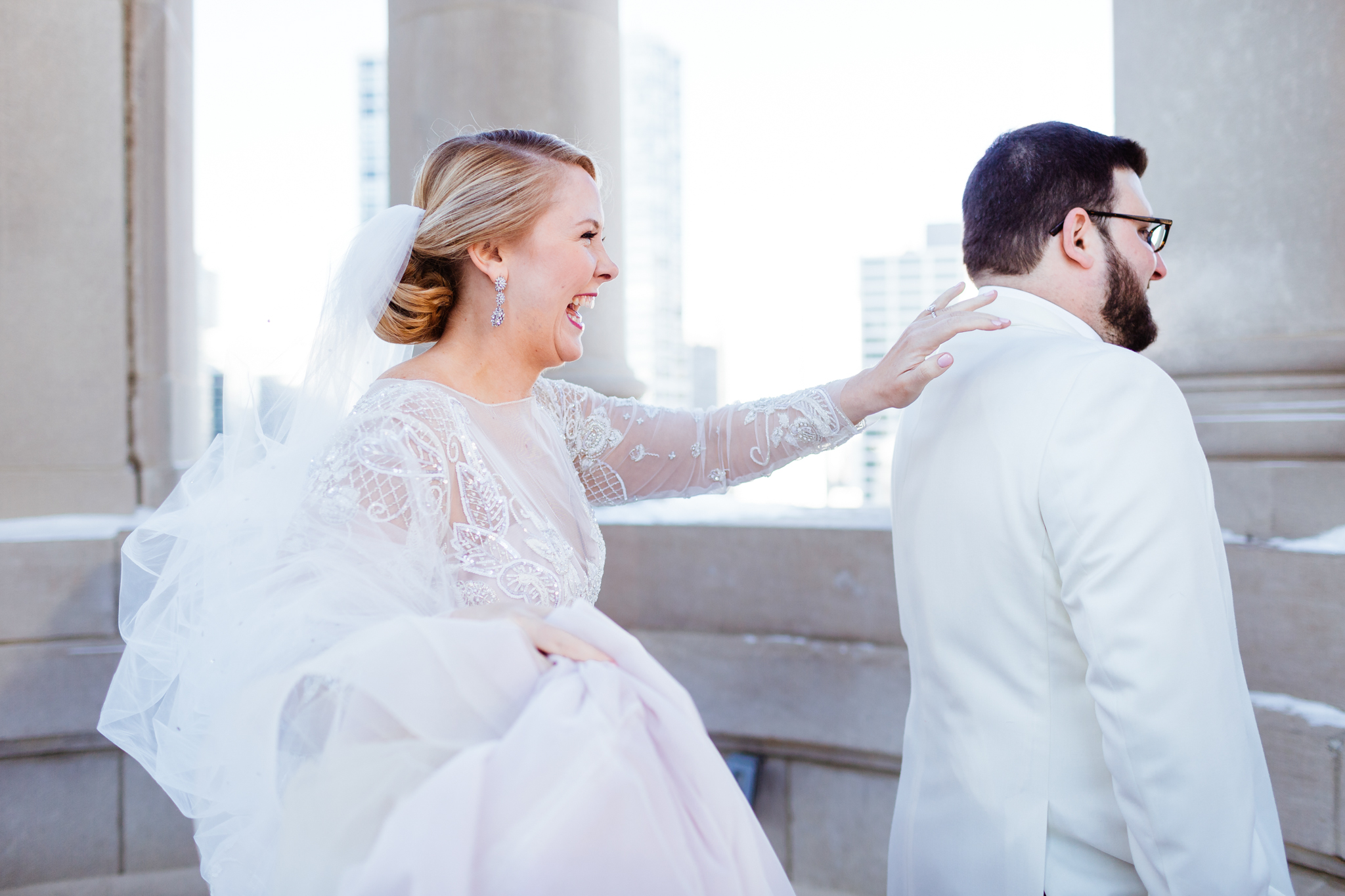 Bride tapping on groom's shoulder during first look