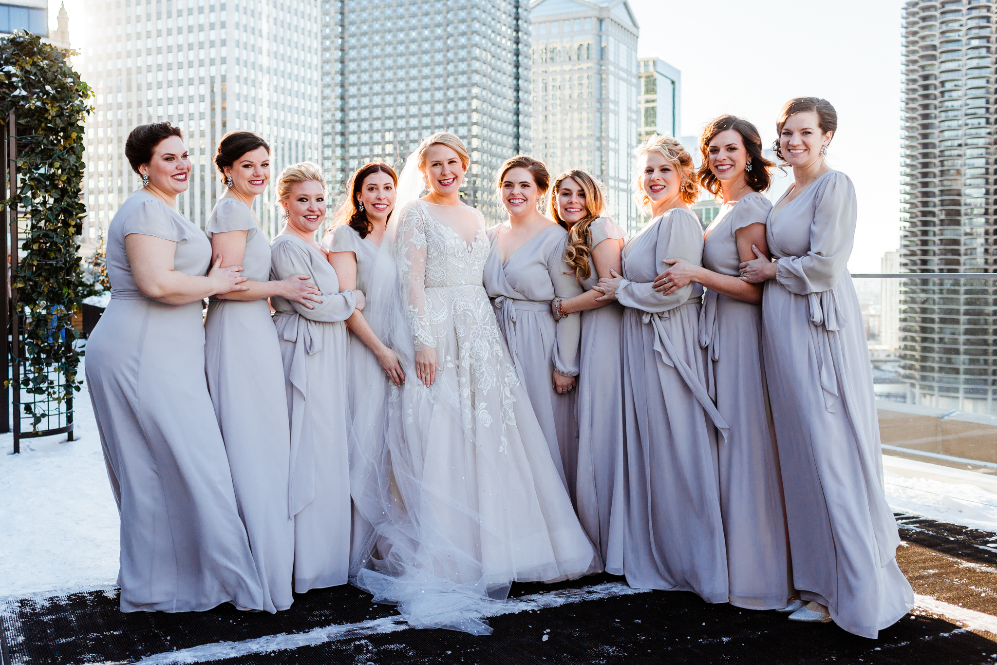 Bridal party in purple with bride in a blush gown