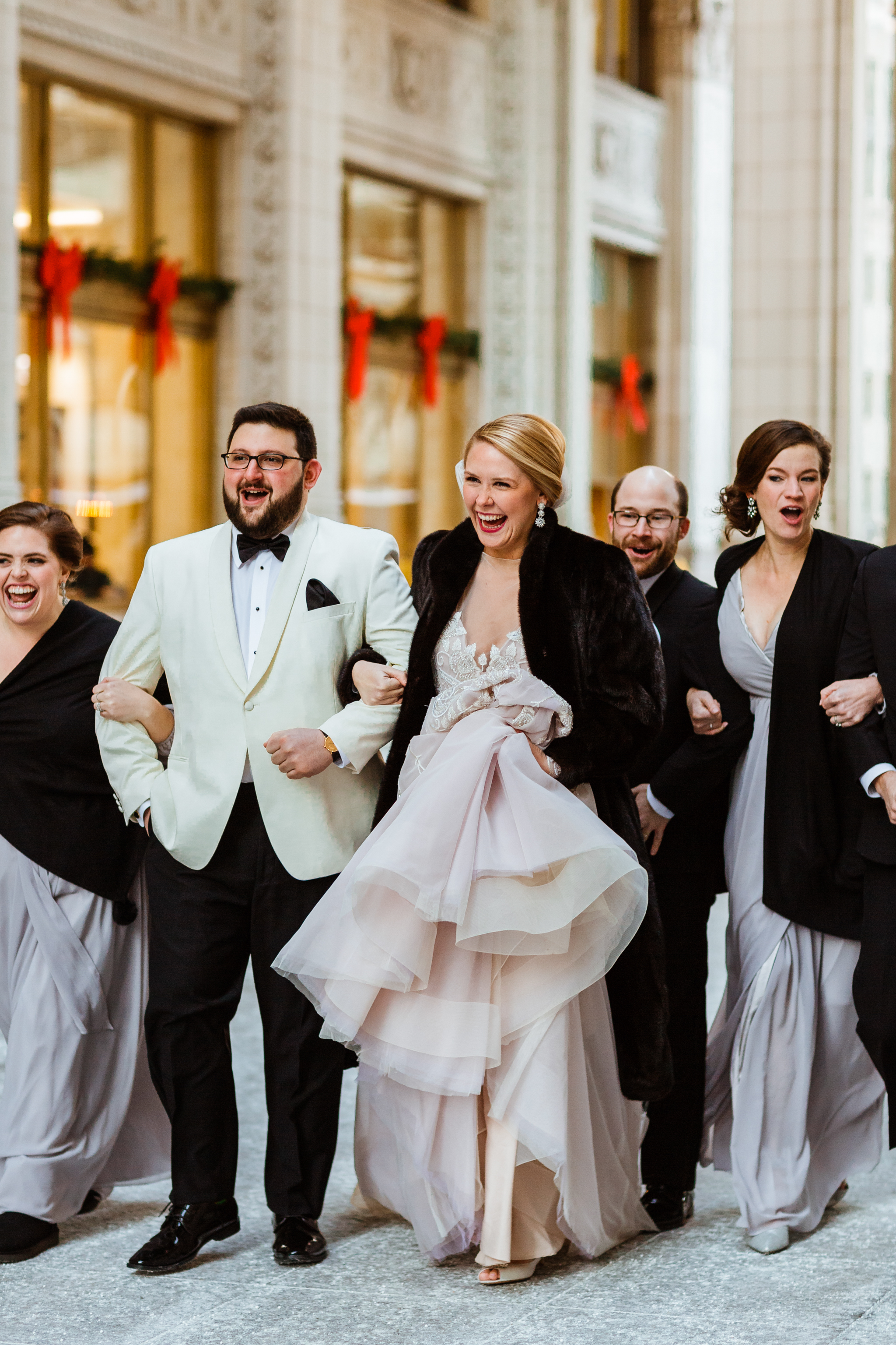 Bridal party running around downtown Chicago taking photographs
