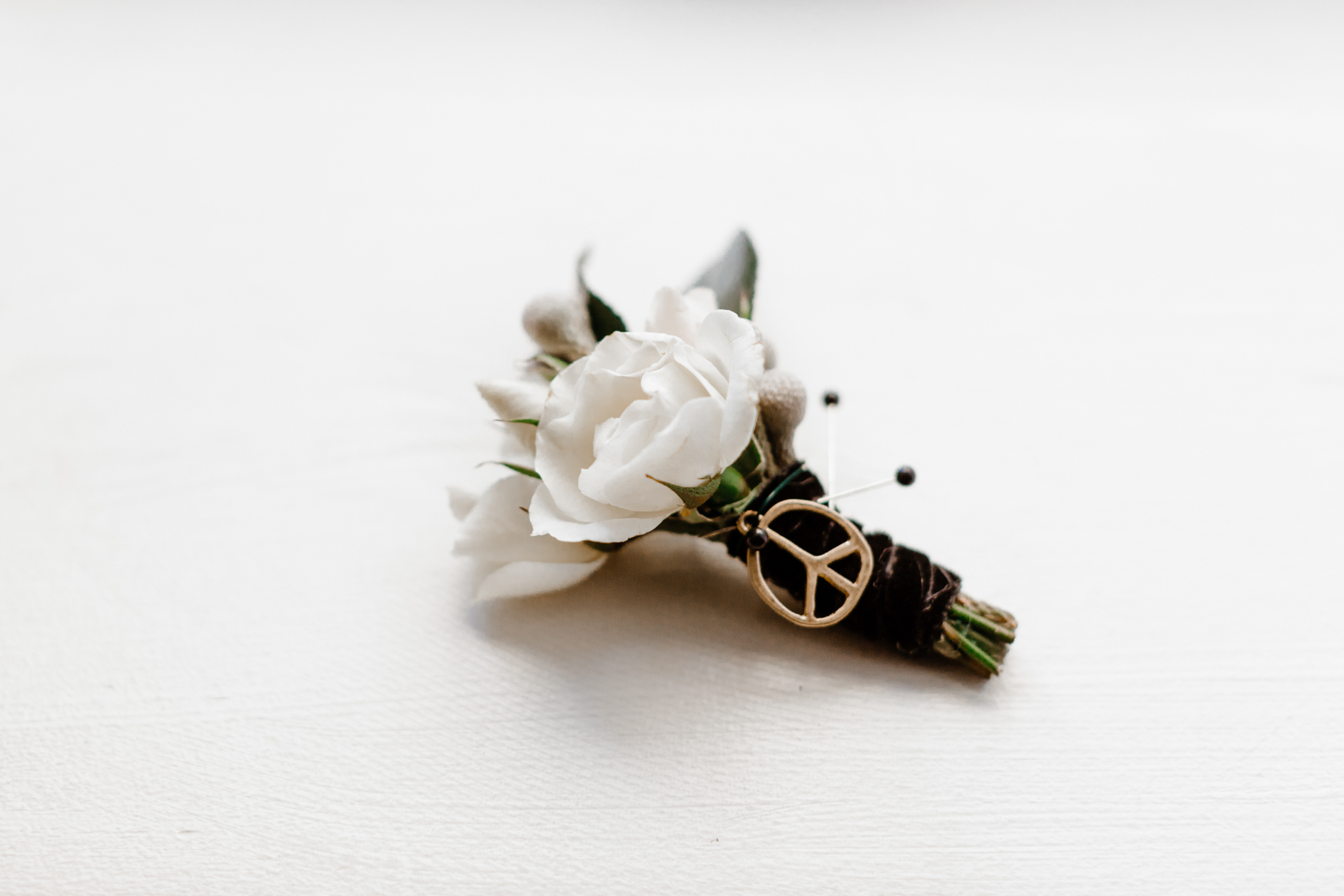 Groom's boutonniere with peace sign charm attached