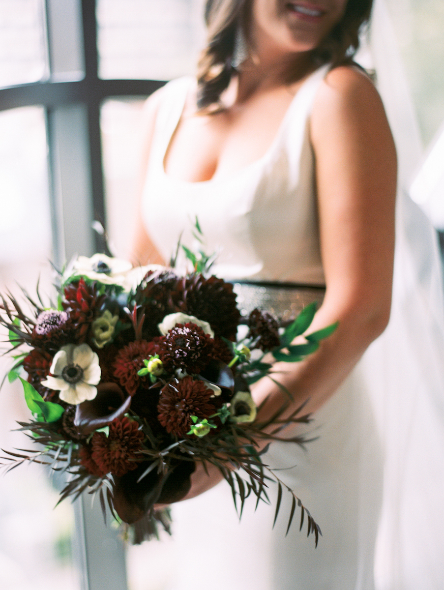Bridal bouquet consisting of maroon dahlias, white anenomes, and greenery