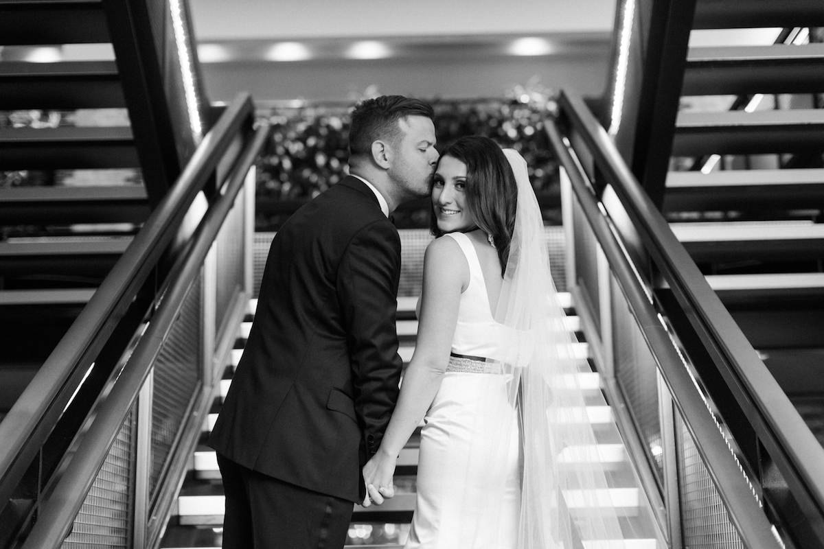 Groom gives blushing bride a kiss on the forehead at the Thompson Chicago hotel