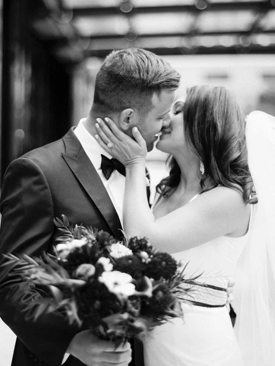 Bride and groom share a kiss with bridal bouquet in tow