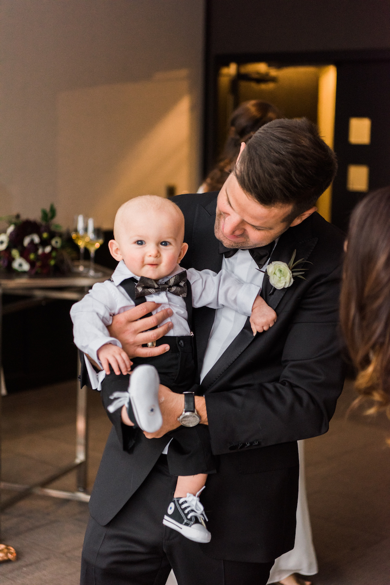 Adorable ring bearer in bowtie, chuck taylors, and suspenders