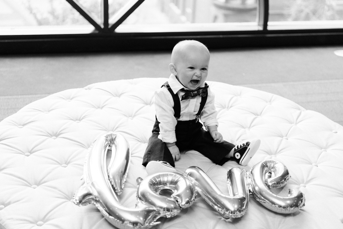 Bride and Groom's son with love balloons on couch