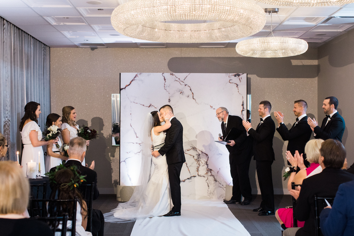 Bride and Groom share a kiss at wedding with chandeliers and marble backdrop