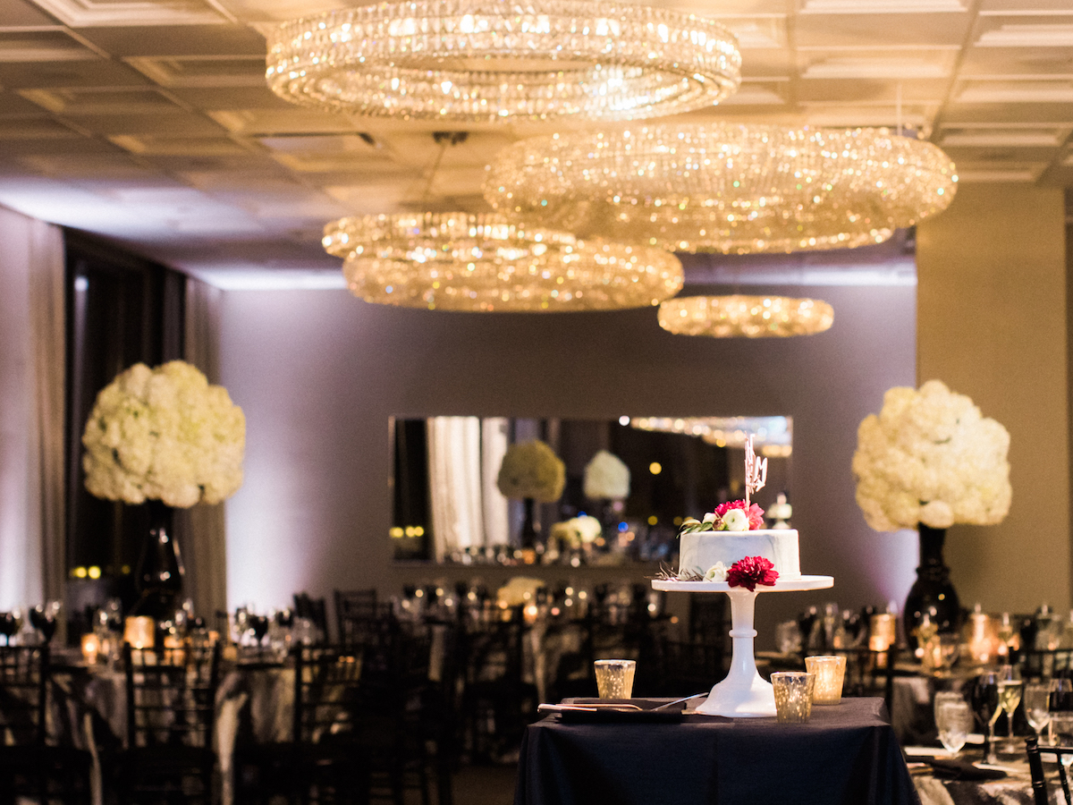 Wedding cake surrounded by chandeliers and hydrangea centerpieces
