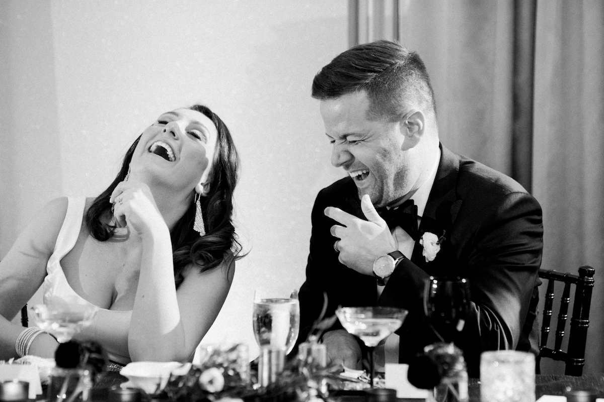 Bride and groom laughing during a speech at a wedding reception