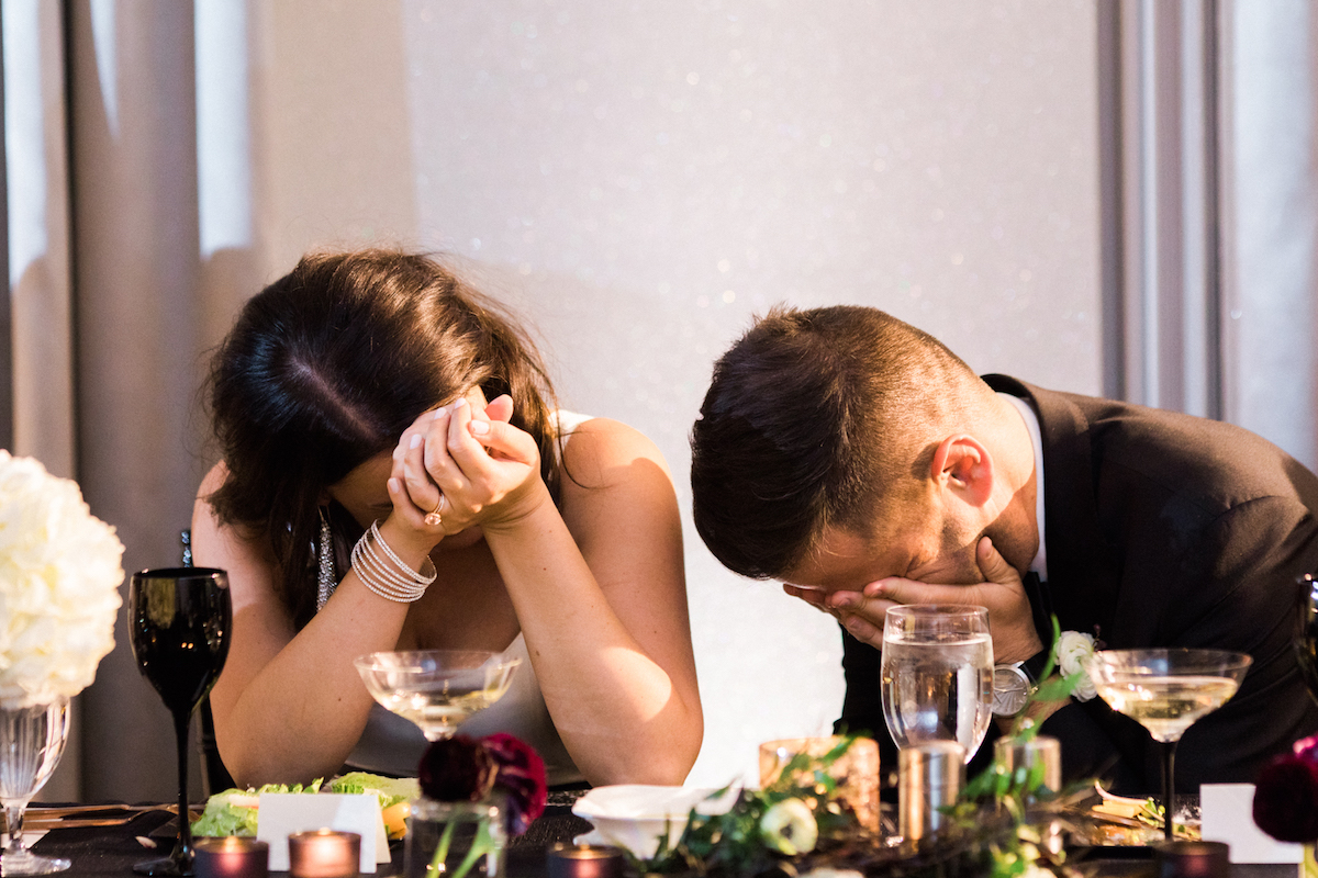 Bride and groom sharing embarrassment during speech at wedding