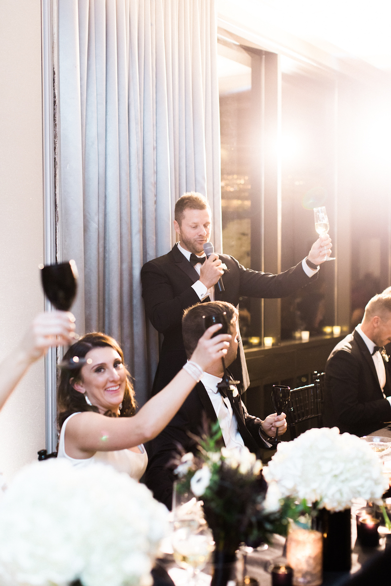Bride and groom offering cheers during best man toast