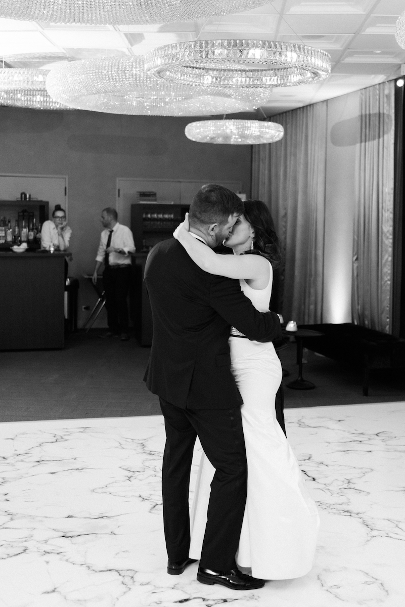 Bride and groom kiss on marble dance floor during first dance