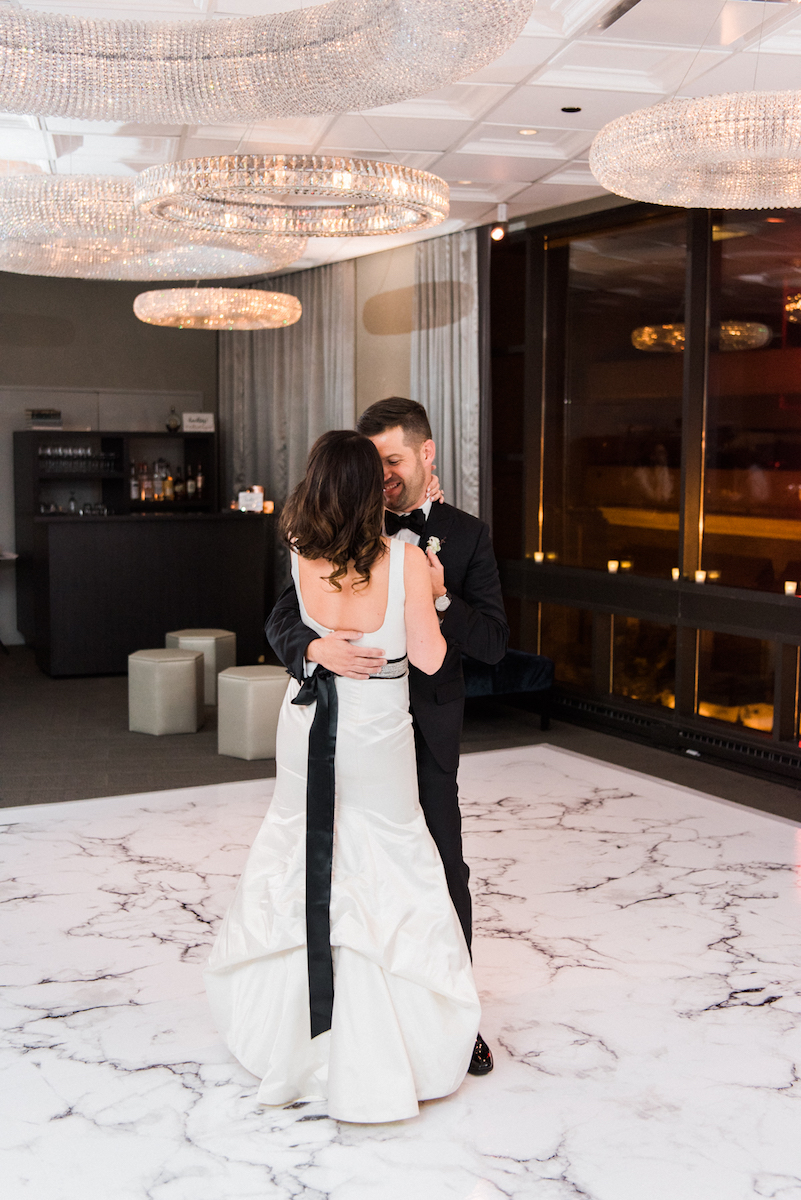 Bride and groom share first dance on marble dance floor surrounded by circular chandeliers