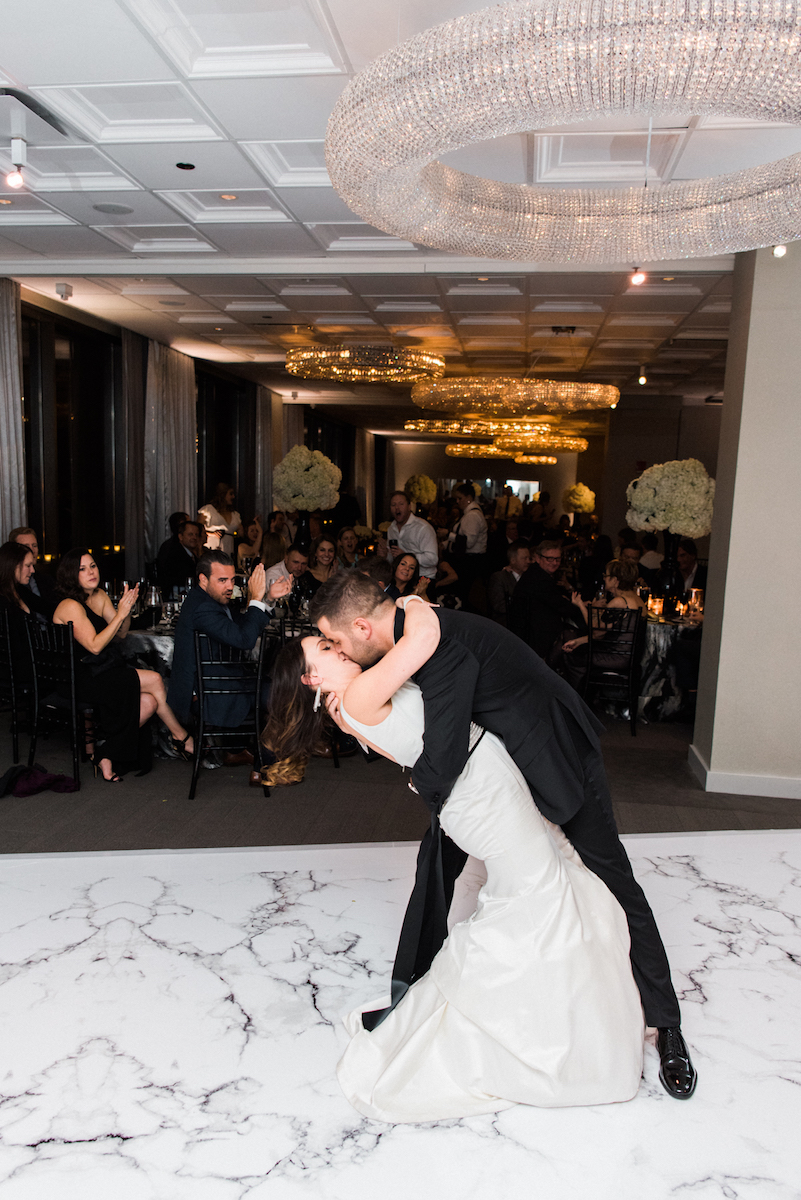 Bride and groom dip and kiss on marble dancefloor at Chicago wedding