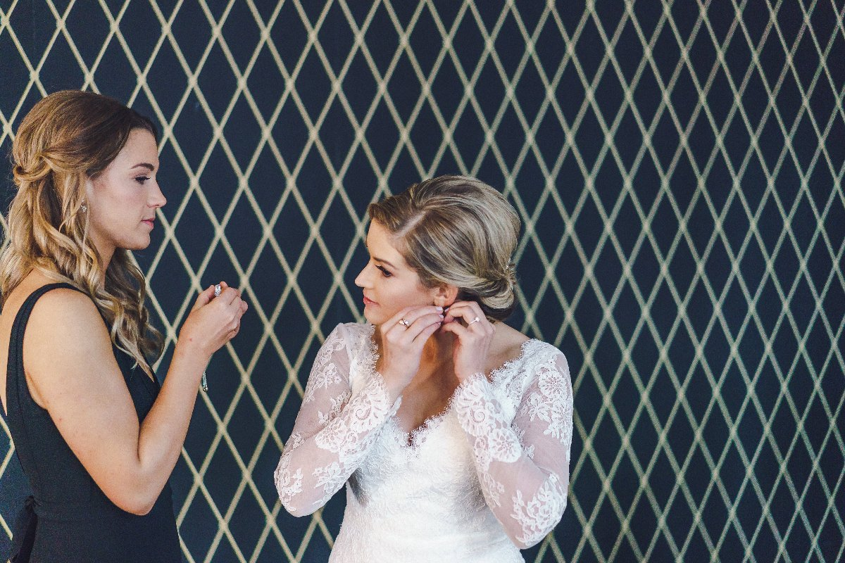 Bride puts on earrings next to her sister