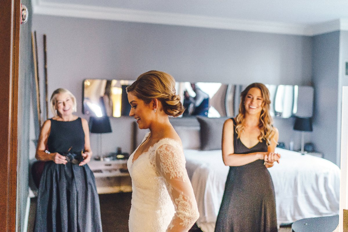Blushing bride in hotel room with mother and sister