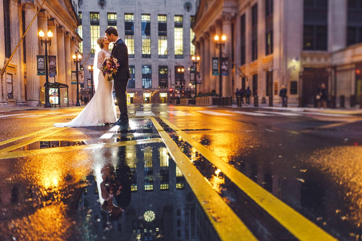 Bride and groom reflection in a rainy puddle