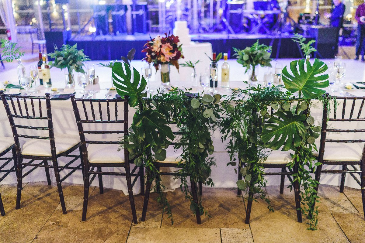 Head table chairs covered in greenery